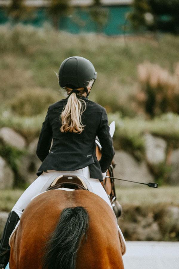 niña montando a caballo en un cocnurso de salto