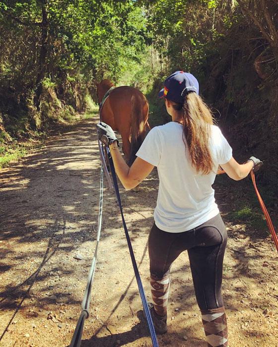 Marta Martínez, fisitaerapeuta y quropractica equina paseando un caballo añlazán por el campo con riendas largas
