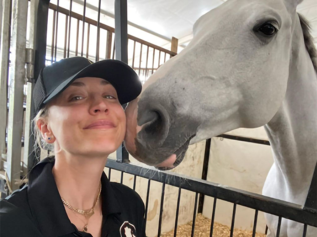 Kaley Cuoco, actriz estadounidense, posando sonriente junto a un caballo tordo en su cuadra