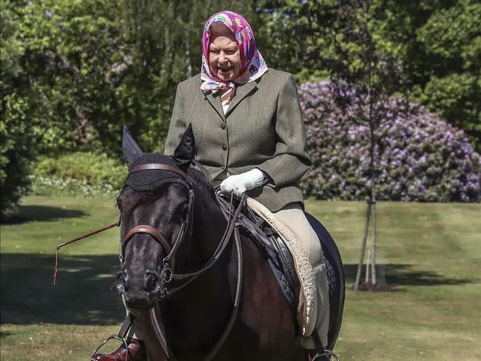 Reina Isabel segunda de Reino Unido montando un poni negro de raza fell a los 94 años en el parque windsor