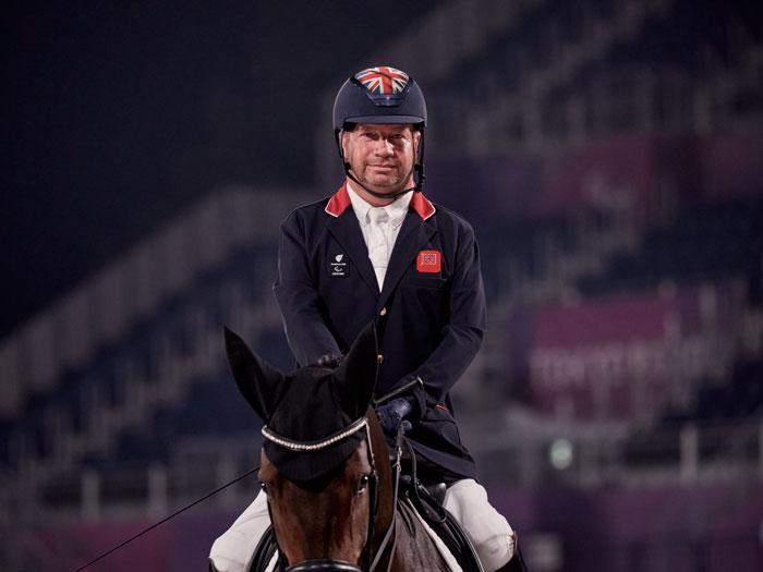 Lee Pearson, jinete paralímpico de grado III, montando a su caballo Breexzer en la pista de competición de Tokio 2020
