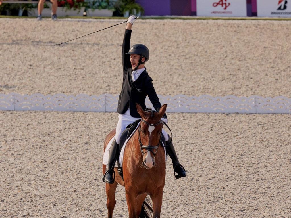 jinete paralímpico letón Rihards Skinus con el brazo en alto mientras monta a caballo saliendo de la pista tras una buena reprise
