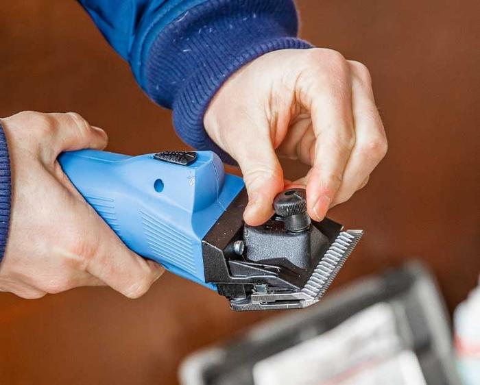 persona ajustando las chuchillas de una maquina para esquilar lister de wahl